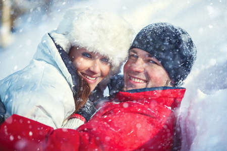 Young happy embracing smiling couple winter outdoors portrait with falling snow. Bright white colors. photo