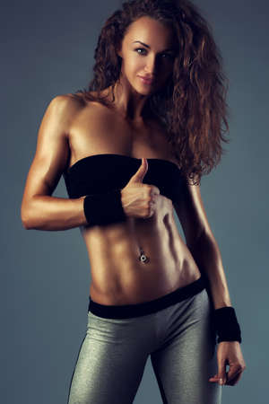 Young brunette slim sports woman showing thumb up. Gray wall background. photo