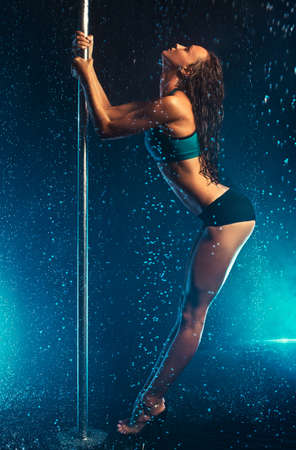 Young slim sexy brunette pole dance woman. Water rain with smoke and blue flares. photo