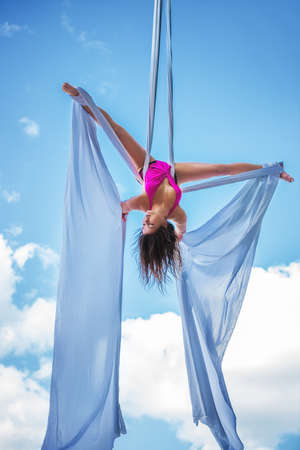 Young brunette woman gymnast upside down on blue sky background.