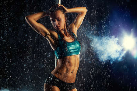 Young slim sexy brunette pole dance woman. Water rain with smoke and flares.