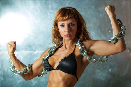 Young sexy sports woman in black lingerie with heavy chain on metallic wall background.