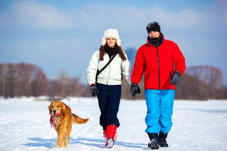 caminando: Pareja joven caminando con el perro. Temporada de invierno fr�o y campo de nieve. Foto de archivo