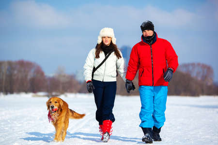 Young couple walking with dog. Cold winter season and snowfield. photo