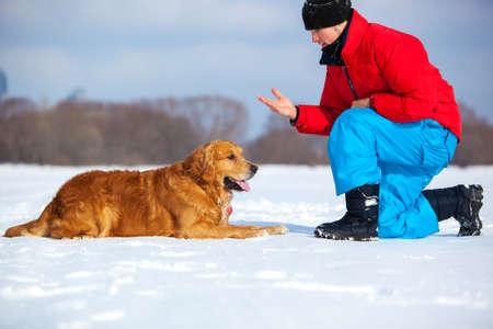 Young man training dog. Cold winter season. photo