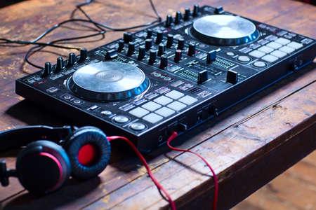 나무 테이블 근접에 헤드폰 DJ 믹서.