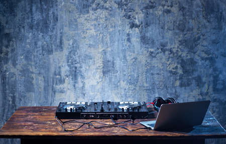 audio mixer: Dj mixer with headphones and laptop on wooden table close-up. Stock Photo
