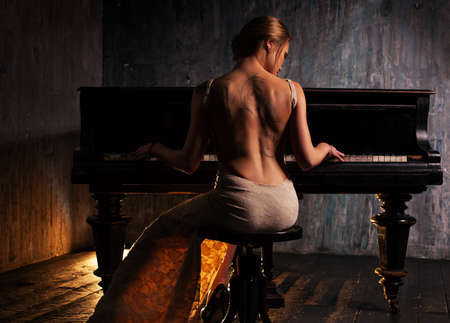 naked woman sitting: Young elegant woman in evening dress with naked back playing piano in retro style interior. Dark colors and backside view.