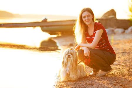 mujer con perro: Mujer joven con el perro shih-tzu sentado en la orilla del lago. La luz del atardecer rojo.