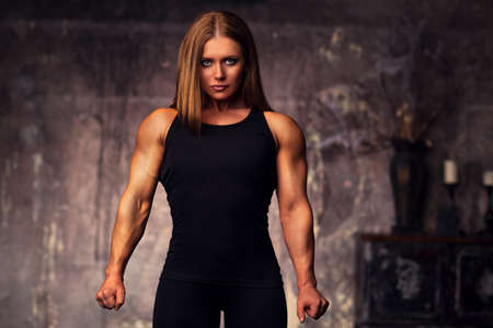 Young strong woman bodybuilder in black clothing standing on retro wall background. photo