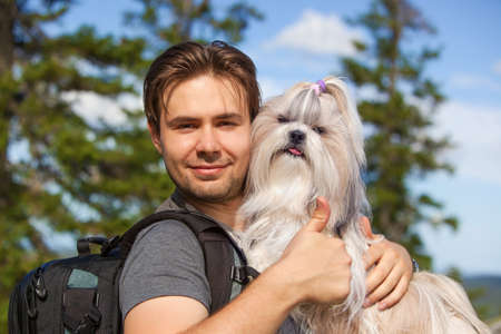 handsign: Young smiling man tourist with shih-tzu dog portrait. Showing thumbs up handsign.