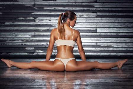 mujer desnuda sentada: Joven mujer sexy delgado deportes en la ropa interior que estira las piernas en el fondo de la pared. Foto de archivo