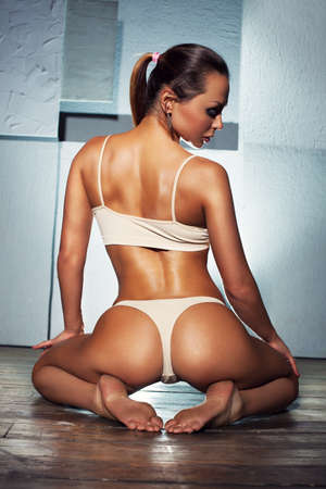 Young sexy slim sports woman in white lingerie sitting on wall background. Backside view. photo