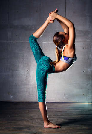 nude gymnast: Young slim gymnast woman in sports clothing stretching legs on wall background.