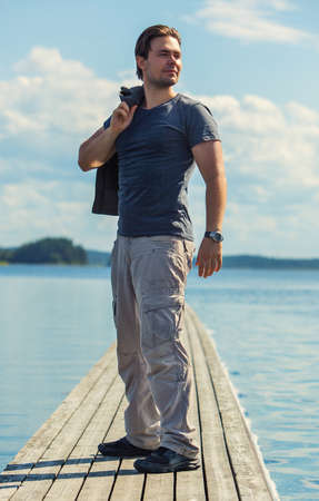 aside: Young man standing on wooden bridge and looking aside