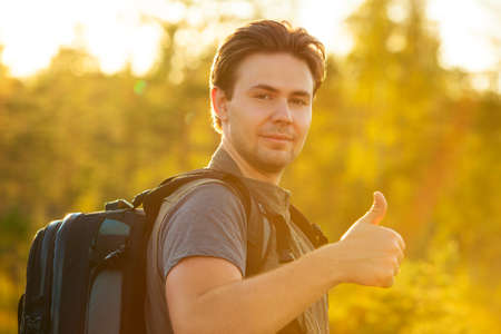 handsign: Young man tourist with backpack showing thumbs up handsign. Red sunset light.