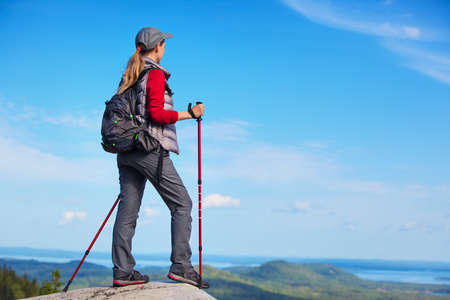 looking aside: Young woman tourist standing on mountain top and looking aside. Stock Photo