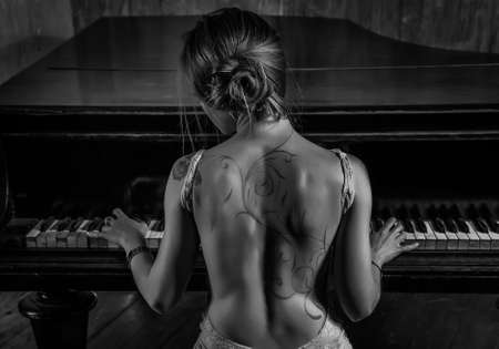nude woman back: Young elegant woman in evening dress with naked back playing piano. Tattoo on back and black and white dark colors. Stock Photo