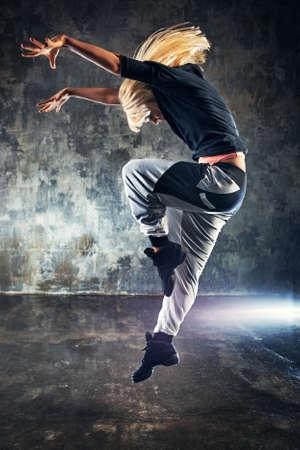 bailarina: Mujer joven moderna saltar bailar�n. El fondo de la pared de piedra oscura.