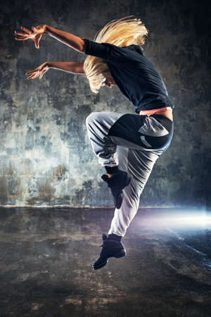 dancer: Young woman modern dancer jumping. On dark stone wall background. Stock Photo