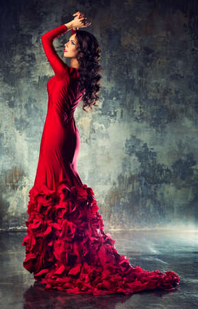 sexy fashion: Young slim sexy fashion woman in long red dress standing on stone wall background