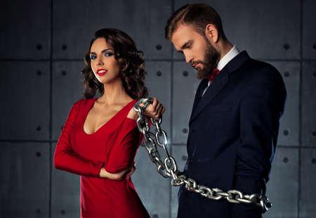 in chains: Mujer feliz joven que coge al hombre y lo sostiene en la cadena pesada. Ropa de noche elegante.