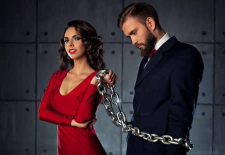 catching: Young happy woman catching man and holding him on heavy chain. Elegant evening clothing.