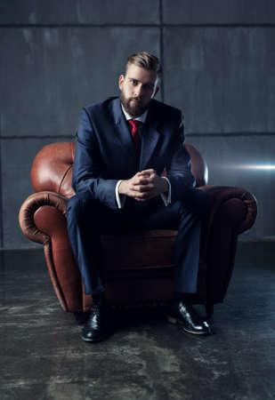 Apuesto hombre de negocios joven con barba en traje negro sentado en una silla y mirando a la cámara. Foto de archivo