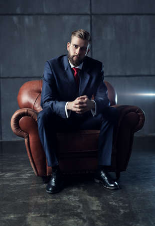 chair: Young handsome businessman with beard in black suit sitting on chair and looking on camera. Stock Photo
