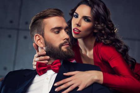 Jeune élégant couple portrait. Femme en rouge homme étreinte. Focus sur l'homme.