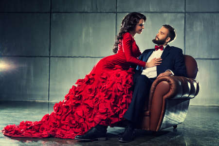 woman red dress: Young elegant loving couple in evening dress portrait. Woman in red and man in black suit sitting on chair.