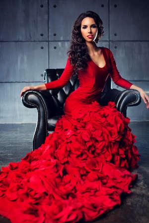 traje de gala: Mujer atractiva delgada joven de moda en el vestido largo de color rojo sentado en silla.