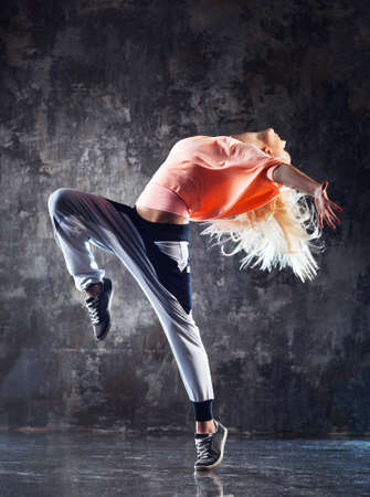 Young woman modern dancer. On stone wall background. Banque d'images