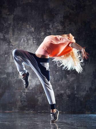 Mujer joven bailarina de danza moderna. El fondo de la pared de piedra.