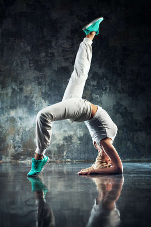 hip hop pose: Young woman modern dancer in white. On dark stone wall background.