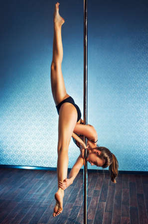 pole dance: Young slim pole dance woman making splits upside down. Stock Photo