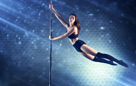 light blue lingerie: Young slim pole dance woman flying on pole. Special light rays and spots motion effect.