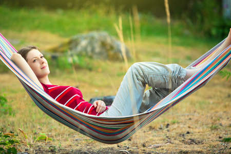 rest: Young woman resting in hammock. Stock Photo