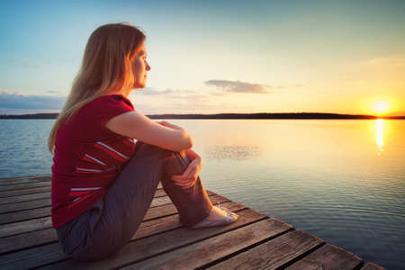 looking aside: Young woman in casual clothing sitting on wooden bridge and looking on sunset over lake.