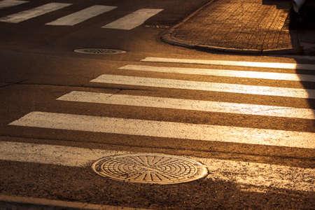paso de cebra: Crosswalk en ciudad en la luz del atardecer.
