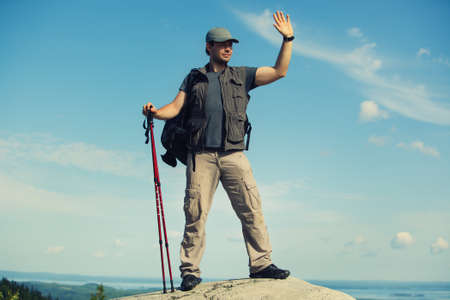 handsign: Young man tourist with backpack and sticks standing on mountain top and waving hand.