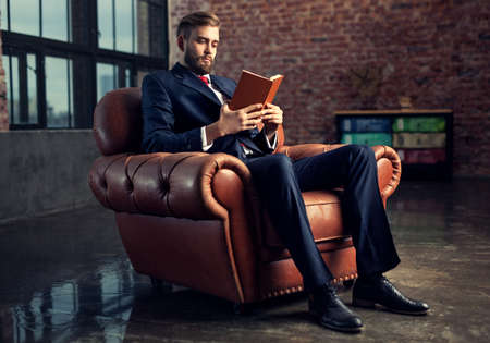 Young handsome businessman with beard in black suit sitting on chair reading book. Focus on face. Stockfoto