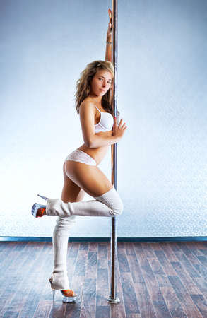 Young slim sexy pole dance woman in white clothing. Bright white colors. photo