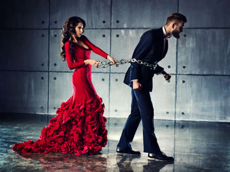 matallic: Young woman in red dress holding man on heavy chain. He tries to escape. Elegant evening clothing. Stock Photo