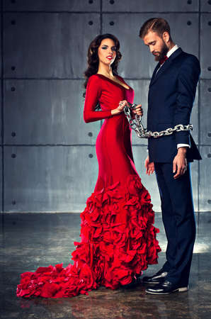 matallic: Young happy woman in red dress holding man on heavy chain. Elegant evening clothing. Stock Photo