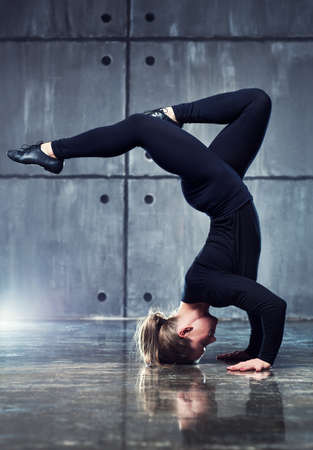 gymnastik: Starke Frau Turner in schwarze Kleidung Stretching auf den Kopf an der Wand Hintergrund.