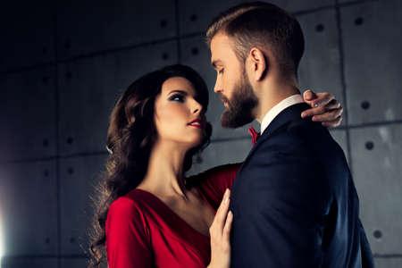 Jeune élégant couple portrait. Femme en rouge homme étreinte.