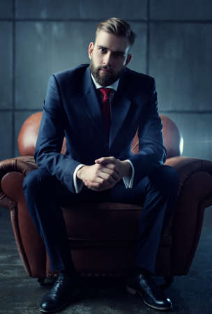 Young handsome businessman with beard in black suit sitting on chair and listens attentively to speaker.