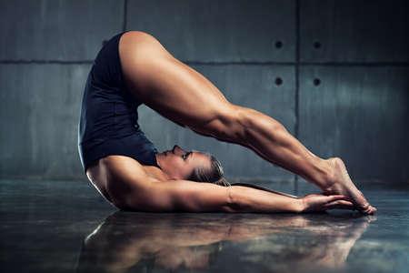 stretching: Mujer culturista fuerte estiramiento boca abajo en el interior urbano.