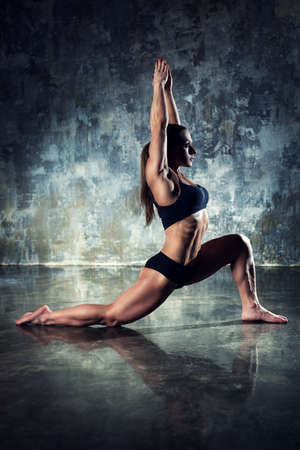 contrast: Strong woman bodybuilder stretching on wall background. Dark contrast colors.